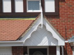 White decorative bargeboards, roof spire with herringbone cladding