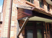 Rosewood UPVC cladding and fascia, brown round guttering on porch in West End